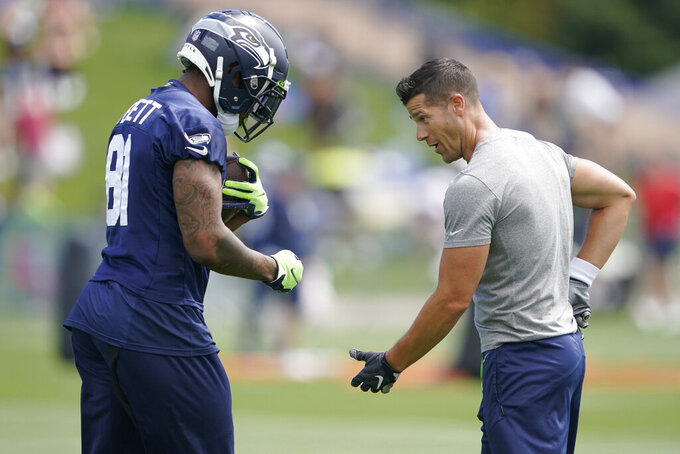 Seattle Seahawks tight end Gerald Everett, left, talks with Dave Canales, right, Seahawks Offensive Passing Game Coordinator, during NFL football practice Wednesday, July 28, 2021, in Renton, Wash. (AP Photo/Ted S. Warren)