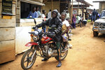 Motorcycle taxi driver Germain Kalubenge transports a woman whose 5-year-old daughter had a fever and was vomiting to an Ebola transit center where potential cases are evaluated, in Beni, Congo, Thursday, Aug. 22, 2019. Kalubenge is a rare motorcycle taxi driver who is also an Ebola survivor in eastern Congo, making him a welcome collaborator for health workers who have faced deep community mistrust during the second deadliest Ebola outbreak in history. (AP Photo/Al-hadji Kudra Maliro)