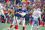 FILE - Buffalo Bills kicker Steve Christie, left, and quarterback Frank Reich celebrates Christie's first quarter field goal against the Houston Oilers at Rich Stadium in Orchard Park, N.Y., in this Sunday, Jan. 4, 1993, file photo. Reich rallied the Bills from a 35-3 deficit to a 41-38 win in overtime. Indianapolis Colts head coach Frank Reich returns to Orchard Park for an NFL wild-card football game against the Bills on Saturday, Jan. 9, 2021.(AP Photo/John Hickey, File)