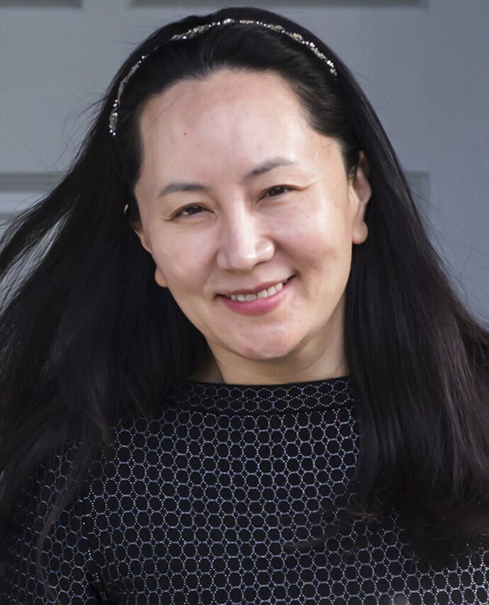 Huawei Chief Financial Officer Meng Wanzhou, who is out on bail and remains under partial house arrest after she was detained Dec. 1 at the behest of American authorities, is accompanied by a private security detail as she leaves her home to attend a court appearance in Vancouver, British Columbia, Wednesday, May 8, 2019. (Darryl Dyck/The Canadian Press via AP)