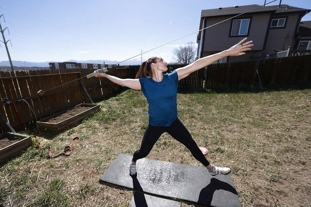 Kara Winger uses a cable system to simulate throwing a javelin as she trains outside her home in Colorado Springs, Colo., Wednesday, April 29, 2020. The renovated home of three-time Olympic javelin thrower Kara Winger now has all the training amenities she needs, including cable. No premium channels on this cable. It's just a basic wire she and her husband installed in the backyard to help her work on her technique. She throws a metal pipe along the angled cable to simulate javelin tosses. (AP Photo/David Zalubowski)
