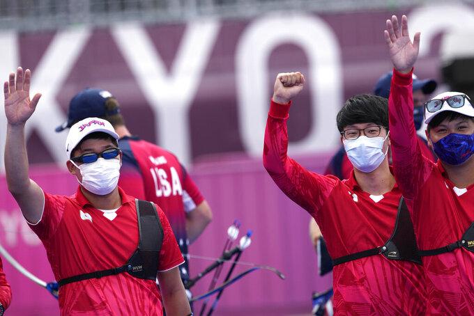Japan's Yuki Kawata, Hiroki Muto, Takaharu Furukawa, celebrate after winning the men's team quarterfinal match against the United States at the 2020 Summer Olympics, Monday, July 26, 2021, in Tokyo, Japan. (AP Photo/Alessandra Tarantino)