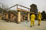 FILE - In this Oct. 10, 2017, file photo a pair of Napa County firemen walk through the remains of a winery in Napa, Calif. The California wildfires are taking a toll on small businesses. (AP Photo/Eric Risberg, File)