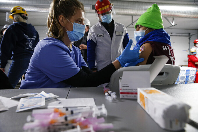 A Tyson Foods team member receives a COVID-19 vaccine from health officials at the Joslin, Ill., facility on Friday, Feb. 19, 2021. A growing number of companies and labor unions are directly securing coronavirus vaccines for their workers. Tyson also has expanded its on-site event to include eligible family members of employees. (John Konstantaras/AP Images for Tyson Foods)