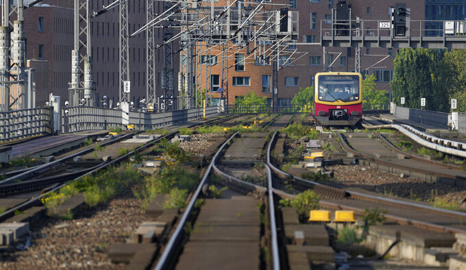 A lonely public train approaches the main station in Berlin, Germany, Thursday, Sept. 2, 2021. A nationwide, five-day train strike has brought big parts of the German railway and commuter system to a standstill. (AP Photo/Michael Sohn)
