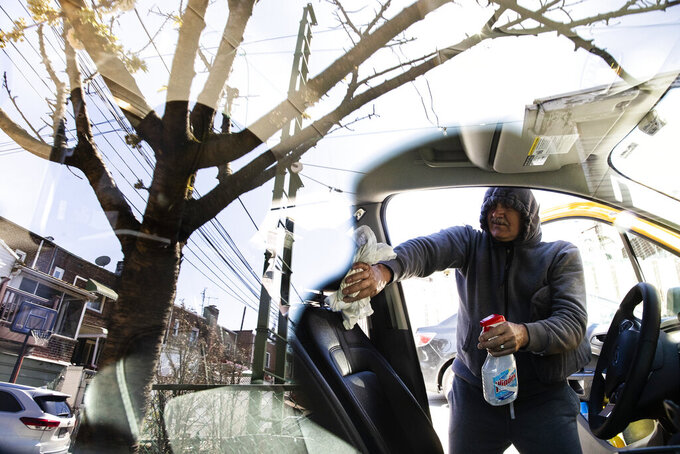 FILE - In this April 6, 2020, file photo, taxi driver Nicolae Hent cleans and disinfects his cab before starting work in New York. A taxi driver's job was already tougher in recent years with the arrival of ride-sharing companies such as Uber and Lyft. The empty streets during the coronavirus pandemic have made things more difficult. (AP Photo/Matt Rourke, File)