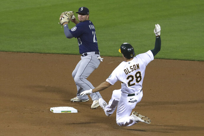 Oakland Athletics' Matt Olson slides into second base as Seattle Mariners' Ty France throws to first base on a double play hit into by Khris Davis during the fourth inning of a baseball game in Oakland, Calif., Friday, Sept. 25, 2020. (AP Photo/Jed Jacobsohn)