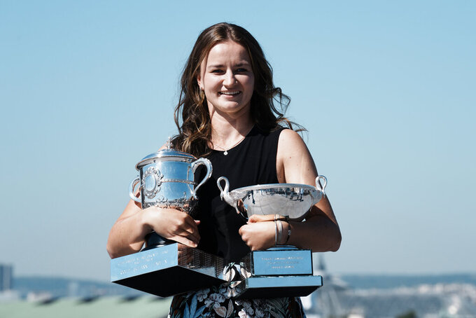 Czech Republic's Barbora Krejcikova holds the French Open tennis tournament women's cup, left, and women's doubles cup during a photocall Monday, June 14, 2021 in Paris. French Open champion Barbora Krejcikova completed a rare sweep of titles at Roland Garros as she won a third women's doubles major trophy with fellow Czech teammate Katerina Siniakova on Sunday. (AP Photo/Thibault Camus)