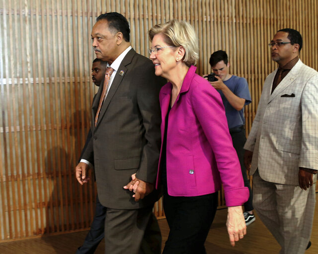 FILE- In this June 29, 2019, file photo, the Rev. Jesse Jackson walks with Sen. Elizabeth Warren, D-Mass., as they attend the Rainbow PUSH Coalition International Convention at Apostolic Faith Church in Chicago. Joe Biden, the presumptive Democratic presidential nominee, is under mounting pressure to pick a black woman in the wake of recent outrage over racial injustice and police brutality. But some black leaders say Warren's progressive politics, economic populism and specific policy proposals addressing everything from maternal mortality to the coronavirus could put her in a strong position. (Kevin Tanaka/Chicago Sun-Times via AP, File)