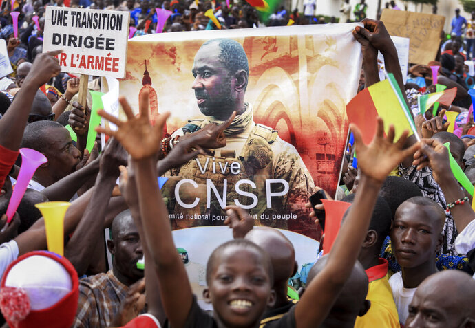 People hold a banner showing Col. Assimi Goita, leader of the junta which is now running Mali and calls itself the National Committee for the Salvation of the People, as they demonstrate to show support for the junta in the capital Bamako, Mali, Tuesday, Sept. 8, 2020. Placard at left in French reads