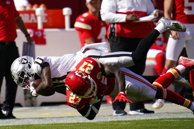 Las Vegas Raiders wide receiver Henry Ruggs III (11) catches a pass over Kansas City Chiefs cornerback Rashad Fenton (27) during the first half of an NFL football game, Sunday, Oct. 11, 2020, in Kansas City. (AP Photo/Jeff Roberson)