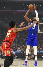 Los Angeles Clippers forward Paul George, right, shoots while Atlanta Hawks forward Cam Reddish defends during the first half of an NBA basketball game in Los Angeles, Saturday, Nov. 16, 2019. (AP Photo/Kelvin Kuo)