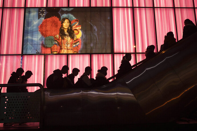 Shoppers at a retail district pass by an American lingerie company Victoria's Secrets store in Beijing on Friday, Dec. 13, 2019. China deputy trade envoy says China, U.S. have reached trade deal, will reduce punitive tariffs on each other's goods. (AP Photo/Ng Han Guan)