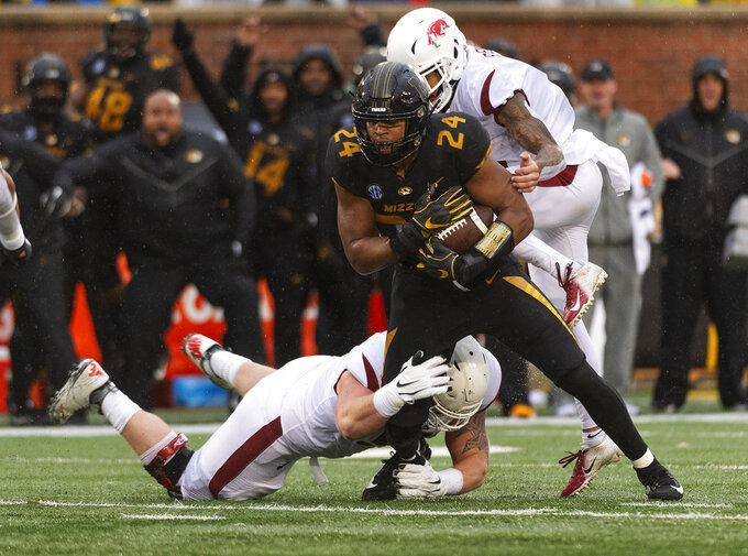 Missouri linebacker Terez Hall, center, intercepts the ball between Arkansas's Deon Stewart, right, and Hjalte Froholdt, bottom, during the first half of an NCAA college football game Friday, Nov. 23, 2018, in Columbia, Mo. (AP Photo/L.G. Patterson)