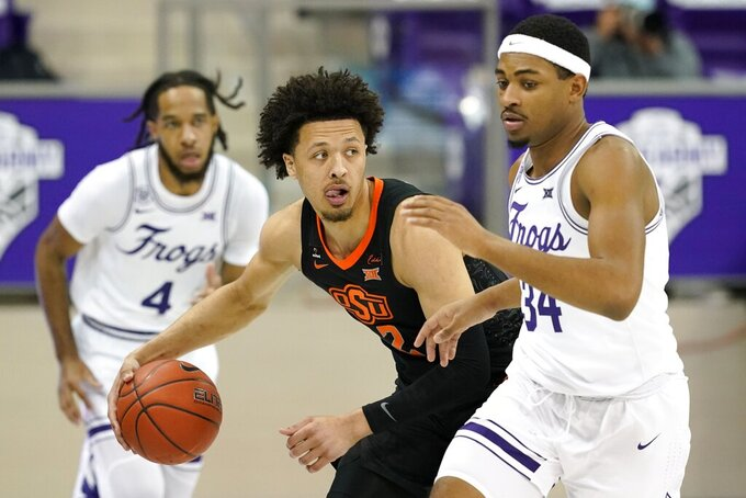 Oklahoma State guard Cade Cunningham (2) advances the ball up court as TCU's Kevin Easley (34) defends in the first half of an NCAA college basketball game in Fort Worth, Texas, Wednesday, Feb. 3, 2021. (AP Photo/Tony Gutierrez)