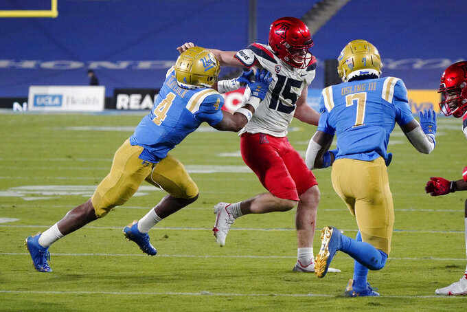 Arizona quarterback Will Plummer (15) runs between UCLA defensive back Stephan Blaylock (4) and defensive back Mo Osling III (7) during the second half of an NCAA college football game Saturday, Nov. 28, 2020, in Pasadena, Calif. (AP Photo/Marcio Jose Sanchez)