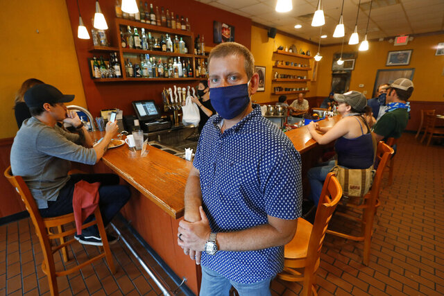 Nick Gavrilides, the owner of the Soup Spoon, poses at one of his two restaurants in Lansing, Mich., Thursday, July 16, 2020. Restaurants, bars and other merchants struggling to stay afloat during the coronavirus pandemic are desperately reaching out for a lifeline from insurers that in turn contend they are being miscast as potential saviors. In one of the first decisions issued on that question, a Michigan state judge sided with an insurer's rejection of a claim for $650,000 for two months of losses that Gavrilides said he suffered at two restaurants. (AP Photo/Paul Sancya)