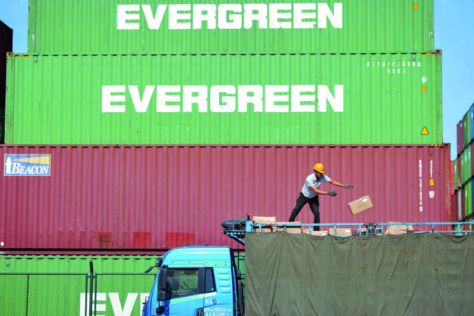 In this Monday, Oct. 14, 2019, photo, a worker loads imported goods on a truck at a distribution company outside the container port in Qingdao in east China's Shandong province. China appealed to Washington for a quick end to their tariff war but gave no indication on Thursday, Oct. 17 what more Beijing might want before it carries out what President Donald Trump says is a promise to buy up to $50 billion of American farm goods. (Chinatopix via AP)