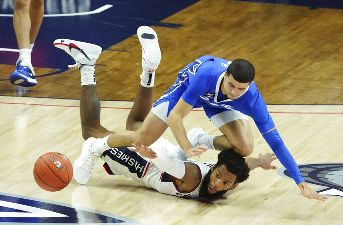 Connecticut guard R.J. Cole, bottom, and Creighton guard Marcus Zegarowski (11) scramble for the ball in the first half of an NCAA college basketball game in Storrs, Conn., Sunday, Dec. 20, 2020. (David Butler II/Pool Photo via AP)