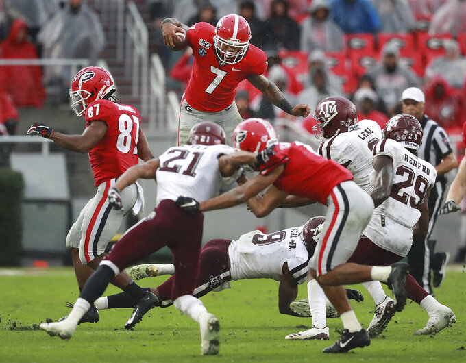 Georgia tailback D'Andre Swift gets some air going over the top of Texas A&M defenders for yardage during the second quarter an NCAA college football game Saturday, Nov. 23, 2019, in Athens, Ga. (Curtis Compton/Atlanta Journal-Constitution via AP)