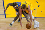Golden State Warriors guard Kelly Oubre Jr., left, reaches for the ball next to Indiana Pacers forward Domantas Sabonis during the first half of an NBA basketball game in San Francisco, Tuesday, Jan. 12, 2021. (AP Photo/Jeff Chiu)