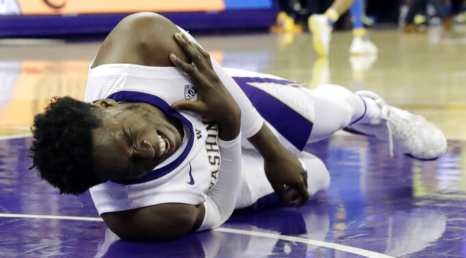 Washington forward Noah Dickerson holds his shoulder after going down with an injury during the first half of an NCAA college basketball game against UCLA, Saturday, Feb. 2, 2019, in Seattle. (AP Photo/Ted S. Warren)