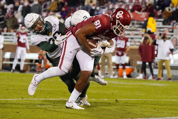 Oklahoma tight end Brayden Willis (81) fights off Baylor defenders Abram Smith, left, and JT Woods for a touchdown during the second half of an NCAA college football game Saturday, Dec. 5, 2020, in Norman, Okla. (AP Photo/Sue Ogrocki)