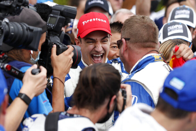NTT IndyCar Series winner Alex Palou, center, celebrates with a team member after taking fourth place in an IndyCar auto race at Grand Prix of Long Beach, Sunday, Sept. 26, 2021, in Long Beach, Calif. (AP Photo/Alex Gallardo)