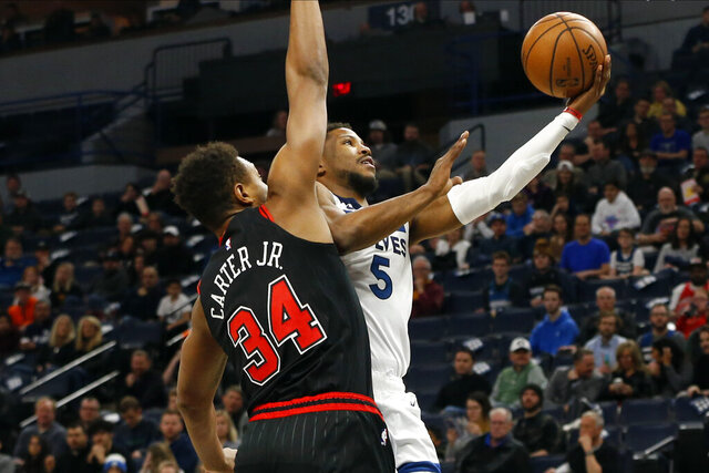 Minnesota Timberwolves' Malik Beasley, right, lays up a shot as Chicago Bulls' Wendell Carter Jr. defends in the first half of an NBA basketball game Wednesday, March 4, 2020 in Minneapolis. (AP Photo/Jim Mone)