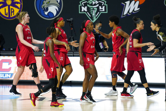 The Las Vegas Aces celebrate their win over the Connecticut Sun during Game 4 of a WNBA basketball semifinal round playoff series Sunday, Sept. 27, 2020, in Bradenton, Fla. (AP Photo/Chris O'Meara)