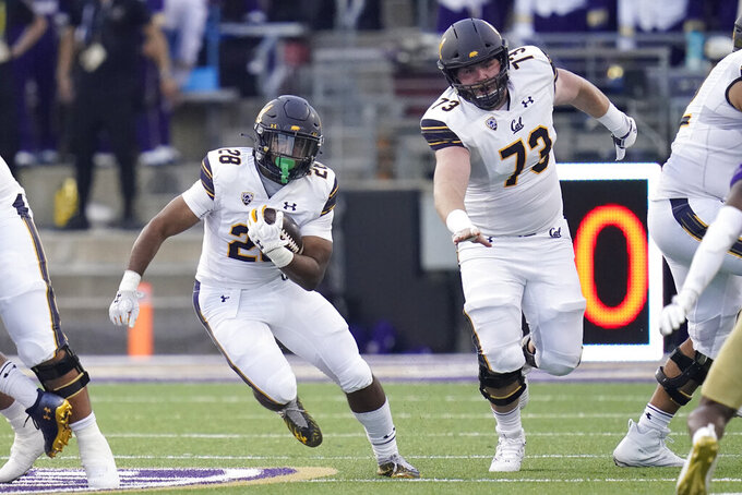 California running back Damien Moore (28) rushes as offensive lineman Matthew Cindric (73) blocks during the first half of an NCAA college football game against Washington, Saturday, Sept. 25, 2021, in Seattle. (AP Photo/Elaine Thompson)