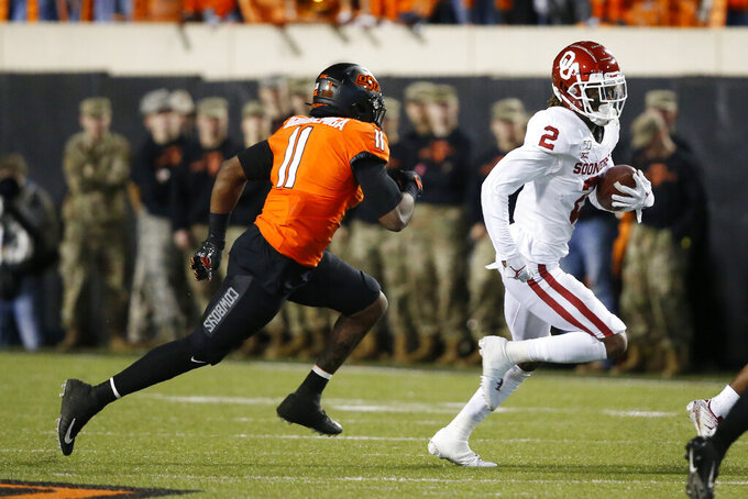 Oklahoma wide receiver CeeDee Lamb (2) is chased by Oklahoma State linebacker Amen Ogbongbemiga (11) in the first half of an NCAA college football game in Stillwater, Okla., Saturday, Nov. 30, 2019. (AP Photo/Sue Ogrocki)