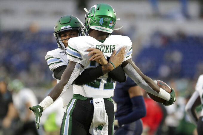 Tulane running back Ygenio Booker, right, is hugged by quarterback Justin McMillan after they connected for a touchdown pass during the second half of an NCAA college football game against Navy, Saturday, Oct. 26, 2019, in Annapolis. Navy won 41-38. (AP Photo/Julio Cortez)
