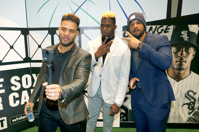 Chicago White Sox's Yoan Moncada, left, Luis Robert, center, and Jose Abreu pose for a video during the team's annual fan convention Friday, Jan. 24, 2020, in Chicago. (AP Photo/Charles Rex Arbogast)