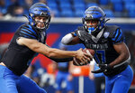 Memphis quarterback Brady White, left, hands the ball to running back Kylan Watkins against the Stephen F. Austin defense during an NCAA college football game on Saturday, Nov. 21, 2020. (Mark Weber/Daily Memphian via AP)