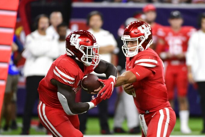 Houston quarterback Clayton Tune (3) hands off to running back Mulbah Car (34) against Texas Tech during the second half of an NCAA college football game Saturday, Sept. 4, 2021, in Houston. (AP Photo/Justin Rex)