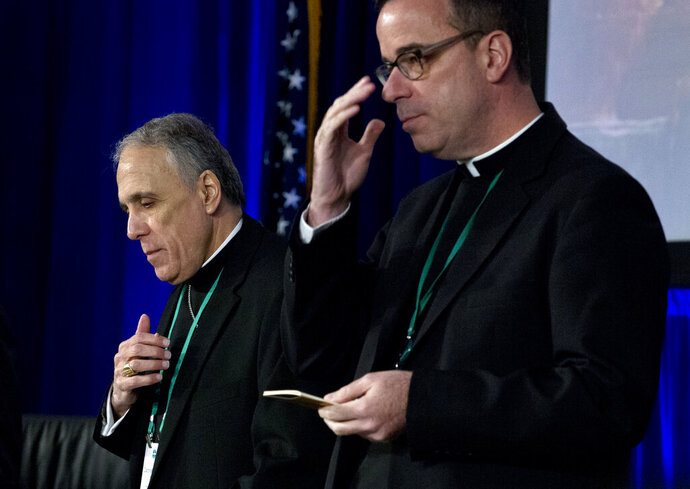 Cardinal Daniel DiNardo, left, of the Archdiocese of Galveston-Houston, president of the United States Conference of Catholic Bishops accompanied by Rev. J. Brian Bransfield, participates in a morning prayer, during the United States Conference of Catholic Bishops (USCCB), 2019 Spring meetings in Baltimore, Tuesday, Jun 11, 2019. (AP Photo/Jose Luis Magana)