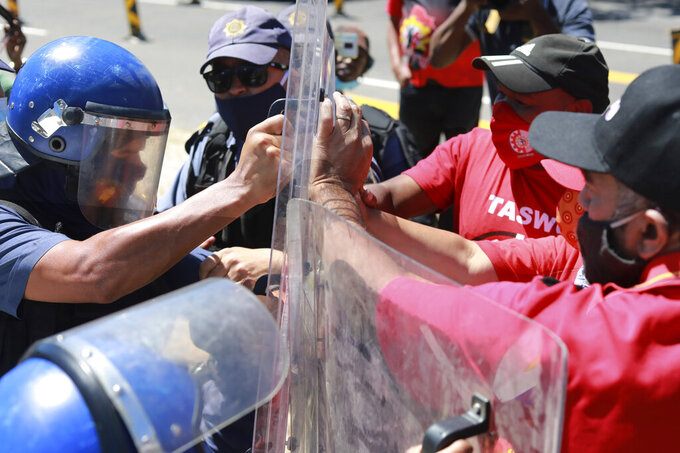 Protesters clash with police at the start of a planned march to Parliament in Cape Town, South Africa, as police stop all protests before they reach parliament Wednesday, Feb. 24, 2021. Various groups planned to protest during Finance Minister Tito Mboweni's 2021 Budget Speech. (AP Photo/Nardus Engelbrecht)