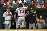Atlanta Braves' Ronald Acuña Jr. (13) high-fives teammates and coaches in the dugout after scoring on Nick Markakis' sacrifice fly during the fifth inning of the team's baseball game against the Washington Nationals, Friday, Sept. 13, 2019, in Washington. (AP Photo/Patrick Semansky)