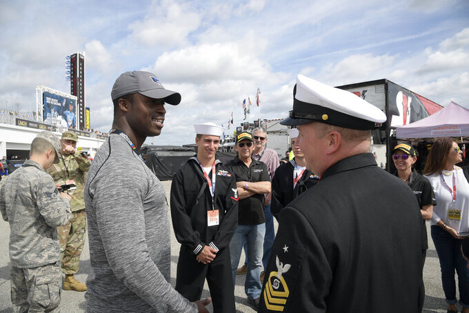 Driver Jesse Iwuji, left, talks to military personal, while leading a tour of the garage area, during a practice session for the NASCAR Daytona 500 auto race at Daytona International Speedway Saturday, Feb. 16, 2019, in Daytona Beach, Fla. (AP Photo/Phelan M. Ebenhack)