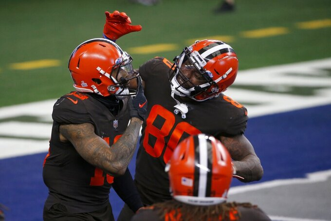 Cleveland Browns wide receiver Odell Beckham Jr. (13), wide receiver Jarvis Landry (80) and others celebrate Beckham's touchdown late in the second half of an NFL football game against the Dallas Cowboys in Arlington, Texas, Sunday, Oct. 4, 2020. (AP Photo/Michael Ainsworth)