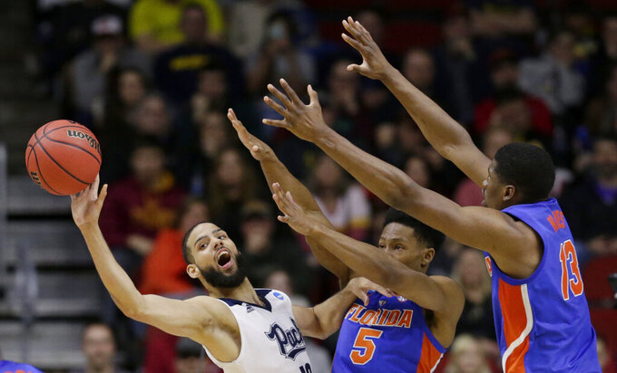 Nevada's Caleb Martin (10) passes the ball away from Florida's KeVaughn Allen (5) and Kevarrius Hayes (13) during the second half of a first round men's college basketball game in the NCAA Tournament in Des Moines, Iowa, Thursday, March 21, 2019. (AP Photo/Nati Harnik)
