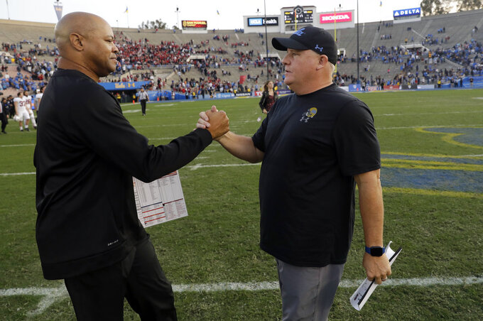 Stanford head coach David Shaw, left, shakes hands with UCLA head coach Chip Kelly after Stanford's 49-42 win during an NCAA college football game Saturday, Nov. 24, 2018, in Pasadena, Calif. (AP Photo/Marcio Jose Sanchez)