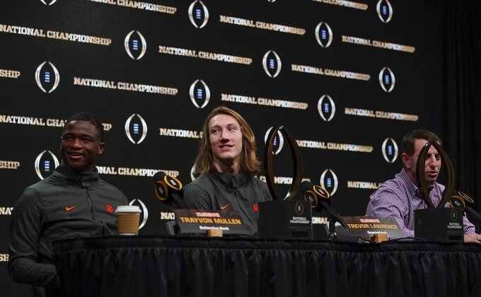 Clemson head coach Dabo Swinney and players Trayvon Mullen and Trevor Lawrence answer questions at a news conference for the NCAA college football playoff championship game Tuesday, Jan. 8, 2019, in San Jose, Calif. (AP Photo/Morry Gash)