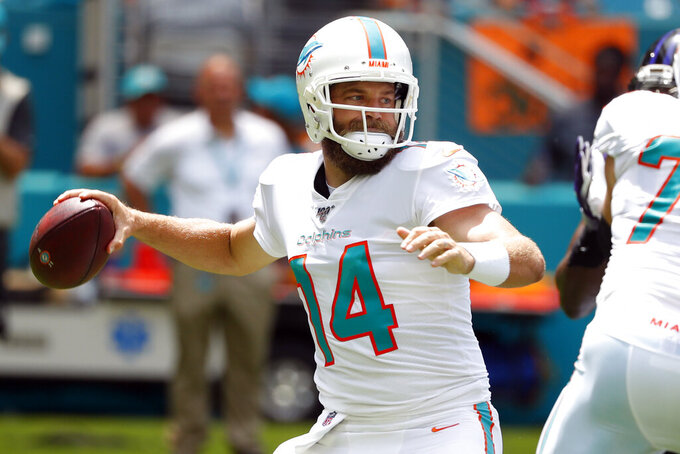 FILE - In this Sunday, Sept. 8, 2019, file photo, Miami Dolphins quarterback Ryan Fitzpatrick (14) looks to pass, during the first half at an NFL football game against the Baltimore Ravens, in Miami Gardens, Fla. Fitzpatrick has been in the NFL so long his oldest sons are now 12 and 10. After games, they want to talk with him mostly about fantasy football. (AP Photo/Wilfredo Lee, File)