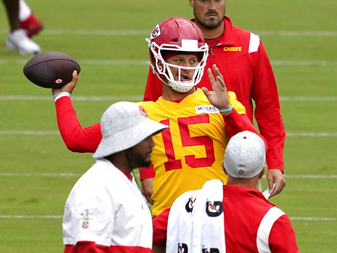 """FILE - Kansas City Chiefs quarterback Patrick Mahomes (15) passes during drills at the team's NFL football training camp in St. Joseph, Mo., in this Saturday, July 31, 2021, file photo. With only a few practices remaining before breaking training camp, the Kansas City Chiefs take a business trip on Saturday to visit the San Francisco 49ers. For quarterback Patrick Mahomes, the results in this first preseason outing matter less than the process.   """"You always like a score, but at the end of the day, I think if the communication, the procedures of in and out of the huddle with so many new guys, especially on that offensive line, I think that would be a win for me just throughout this first game,"""" Mahomes said.(AP Photo/Ed Zurga, File)"""