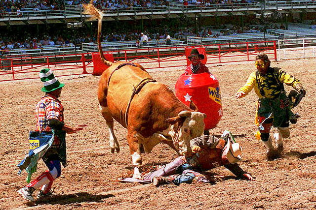FILE - In this July, 1997 file photo, Dwayne Hargo, left, Rick Chatman, right, and Quail Dobbs, in the barrel, try to divert the bull's attention away from a fallen cowboy at the Frontier Days rodeo in Cheyenne, Wyo. Cheyenne Frontier Days has been canceled for the first time in its 124-year history due to the coronavirus. Cheyenne Mayor Marian Orr said Wednesday, May 27, 2020 that organizers decided the risk of spreading the virus was too great for the more than 140,000 people who visit Cheyenne for Frontier Days in late July. (AP Photo/Ed Bailey, File)