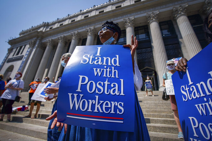 """Retired postal worker Glenda Morris protests postal cutbacks, Tuesday, Aug. 25, 2020, in New York. Postmaster General Louis DeJoy told lawmakers Monday that he has warned allies of President Donald Trump that the president's repeated attacks on the legitimacy of mail-in ballots are """"not helpful,"""" but denied that recent changes at the Postal Service are linked to the November elections. (AP Photo/Robert Bumsted)"""