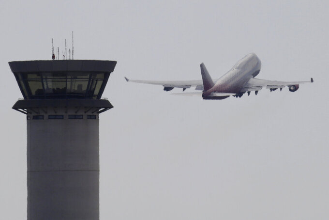 FILE - In this Saturday, Oct. 7, 2017 file photo, an aircraft takes off from Larnaca airport past the control tower, at the southern coastal city of Larnaca, Cyprus. A flight safety organization is warning that a Turkish drone base in ethnically divided Cyprus could increase safety risks for thousands of commercial flights that cross the airspace around the eastern Mediterranean island. FSF-Med, which is affiliated with the International Flight Safety Foundation, said Tuesday, Sept. 14, 2021 the planned upgrade for the Turkish air base in Gecitkale — which is called Lefkoniko in Greek — may compound a communications problem between aviation authorities in Turkey and Cyprus. (AP Photo/Petros Karadjias, file)
