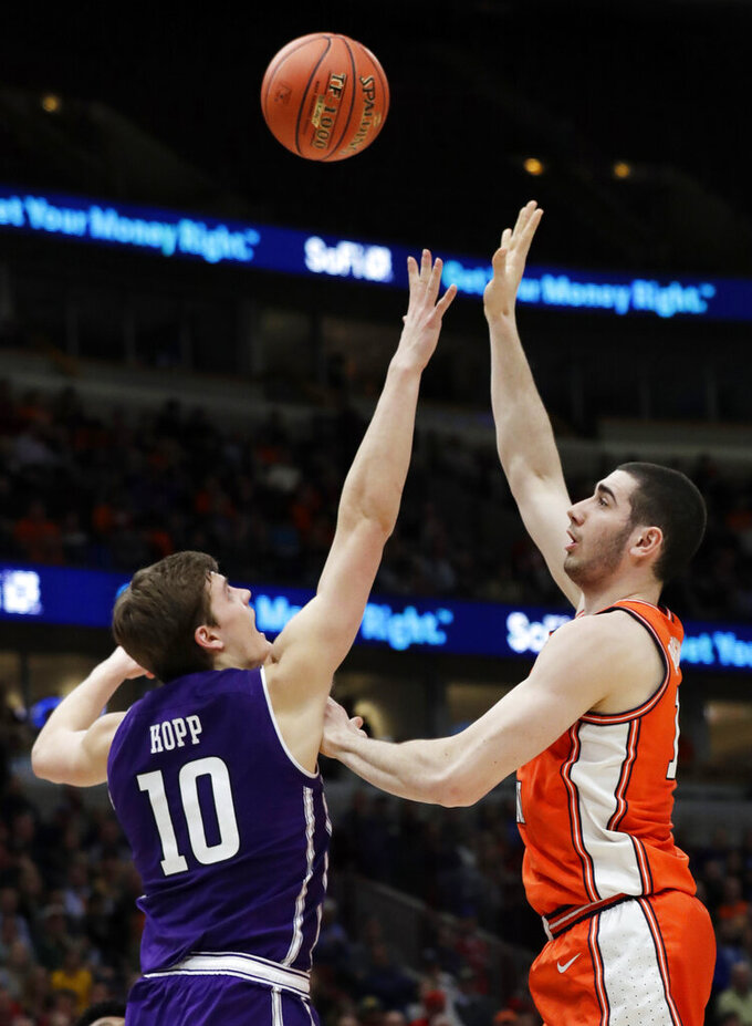 Illinois forward Giorgi Bezhanishvili, right, shoots over Northwestern forward Miller Kopp during the second half of an NCAA college basketball game in the first round of the Big Ten Conference tournament in Chicago, Wednesday, March 13, 2019. Illinois won 74-69 in overtime. (AP Photo/Nam Y. Huh)